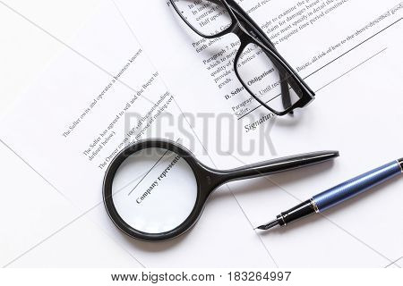 office desk with signing contract, magnifier and feather pen for business top view