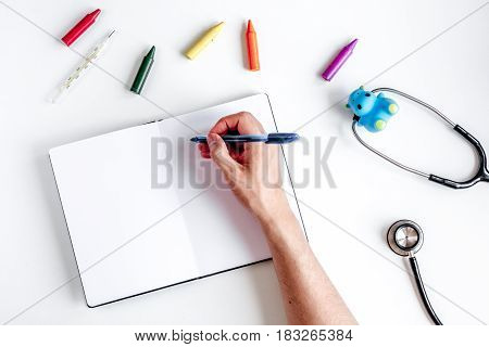 children's doctor work with stethoscope and markers on white desk background top view mock-up