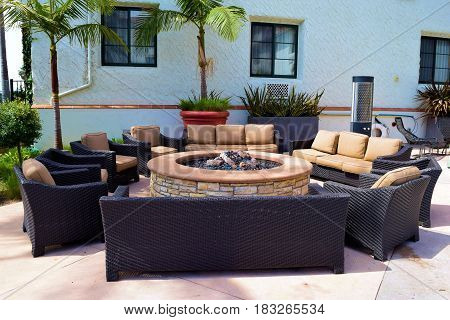 Contemporary style outdoor chairs and sofas surrounding a gas fire pit taken at a courtyard in a residential yard
