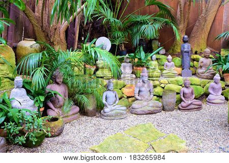 Buddha sculptures beside lush green plants surrounded by pebbles and rocks taken in a rustic spiritual meditation garden