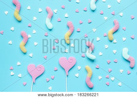 Delicious heartshaped sugar lollipops and candys on blue background top view pattern