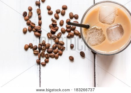 iced coffee with beans for cold summer drink on white wooden table background top view