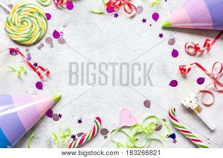 Colored party hat, sweets and confetti on stone table background top view mockup