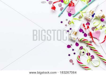Colored party heart-shaped sweets and confetti on white table background top view mockup
