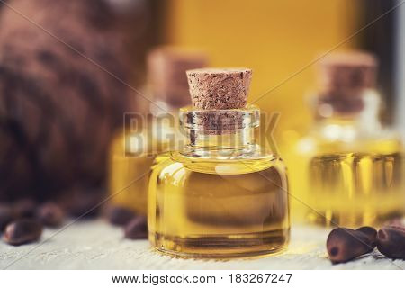 The cedar oil in a glass bottle on a white wooden background. Source of essential fatty acids for healthy nutrition