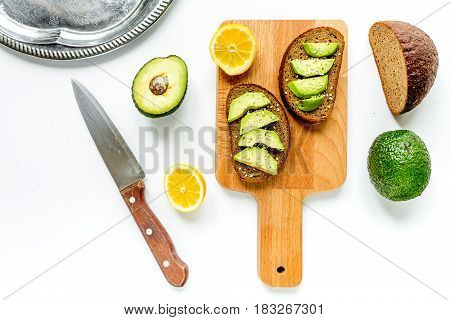 Ingredients for cooking sandwiches with fresh avocado on white kitchen table background top view