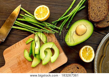 homemade sandwiches with avocado and bread on wooden kitchen table background top view