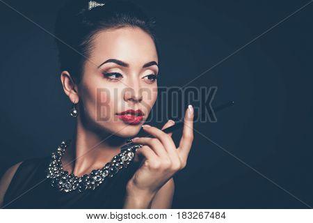 Retro woman portrait, standing on the black background .