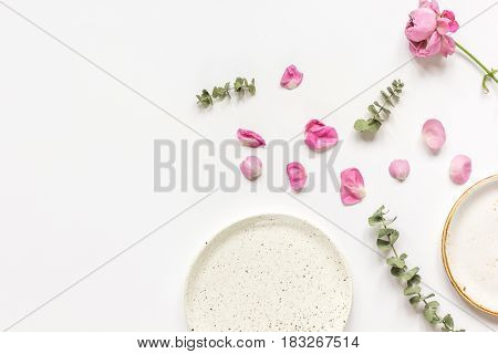 rose petals, eucalyptus and plates in woman table spring design on white background top view mockup