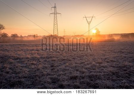 High voltage line supports at early morning in frosty field with old grass shining at sunrise