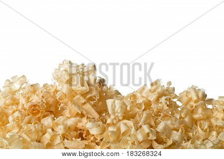 Light brown wood shavings from carpenter's hand planer or chisel work on wooden boards isolated on white background with copy space