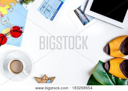 tourist stuff with tablet, ticket and world map on white table background top view mock up,
