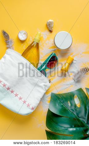 Woman cosmetic set with sun protection lotion and sunglasses for summer seaside rest on orange desk background top view