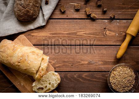 traditional homemade wheat and rye bread with rolling-pin on wooden kitchen table background top view space for text