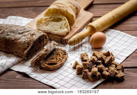 Dried bread crumbs with bread on wooden kitchen table background