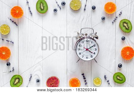 Citrus fruit mockup with lavander, alarm clock and blueberry on white wooden desk background top view