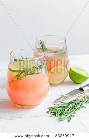 glass of fresh juice with lime and rosemary for healthy drink on white kitchen table background