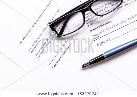 office desk with signing contract, glasses and feather pen for business top view