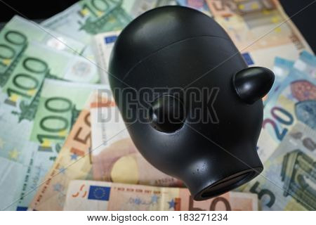 Black piggy bank on pile of Euro banknotes as saving concept.