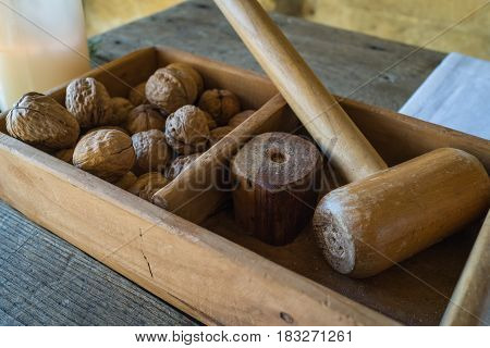 A wooden box with traditional wooden hammer to crack walnuts for italian breakfast.