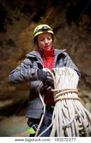 Speleologist performing rope maneuvers in a cave. Zaragoza Province, Aragon, Spain.