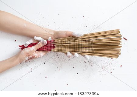 Female hands in powder are holding a bunch of incense sticks on the white background in the studio. Sticks colored in red-brown. Closeup. Horizontal.