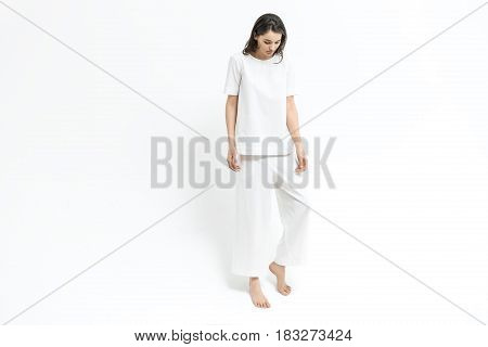 Pretty barefoot girl is posing in the studio on the white background. She wears a white T-shirt and pants. Woman holds left leg on the toe and looks downward. Horizontal.