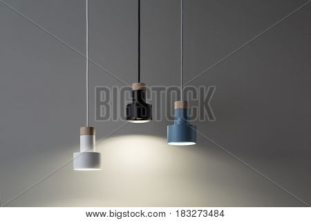 Glowing lamps with light wooden parts are hanging on the cables on the background of the gray wall. They are blue, black and white colored. Closeup. Horizontal.