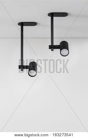 Stylish black lamps are hanging on the ceiling on the gray wall background. Closeup photo. Indoors. Horizontal.