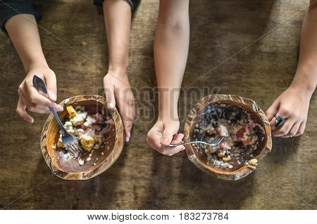 Woman's hands with forks and wooden bowls on the table. In the bowls there are exotic fruit mix. Shoot from above. Closeup. Horizontal.