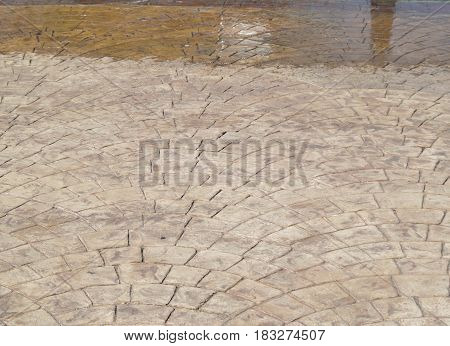 Stamped concrete, light brown oblong shapes in concentric arcs, wet and dry areas due to sprinkler.