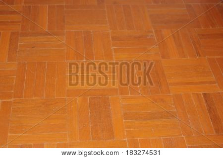 Medium timber color parquet floor with five finger squares at ninety degrees to one another.