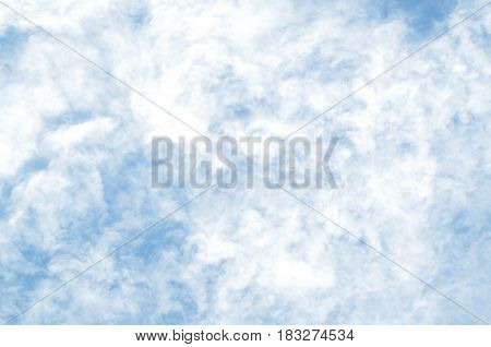 Pale blue sky covered with fluffy white clouds.