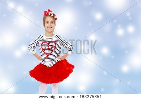 Little girl in a red skirt and bow on her head.She poses with hands on hips.Blue Christmas festive background with white snowflakes.