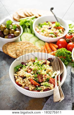 Pearl couscous salad with fresh vegetables and herbs