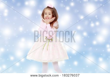 Dressy little girl long blonde hair, beautiful pink dress and a rose in her hair.She holds the palm of your hand near their cheeks.Blue Christmas festive background with white snowflakes.