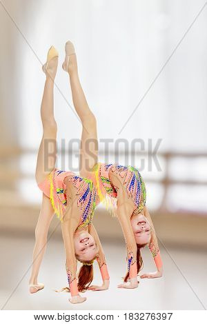Two little twin girls who are doing gymnastics, doing the bridge.In the sports hall with mirror and a large semi-circular window.