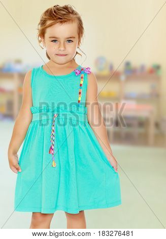 Stylish small, tanned girl in a blue dress with short sleeves. Close-up.In the children's room where there are shelves with toys.