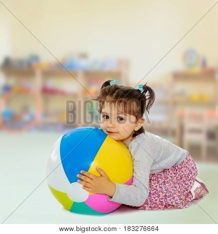 Cute little dark-haired girl with short pigtails on the head, hugging his big , inflatable, striped, vinyl ball.In the room the children's garden where there are shelves with toys and material.