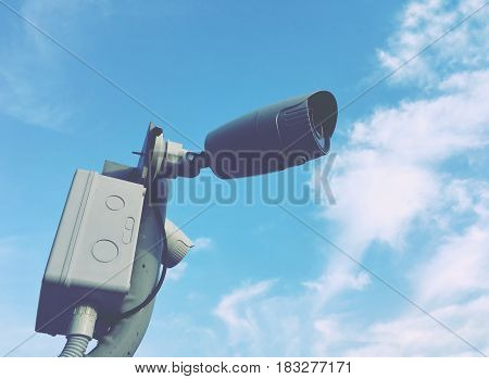 Closed circuit camera on blue sky, vintage background.