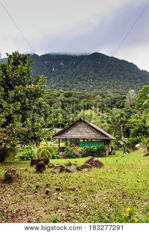 Wooden hut in front of large mountain with lush green surroundings.
