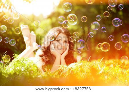 Woman and soap bubbles in park . Positive summertime scene. Happy girl model outdoors Against the background of green grass and trees
