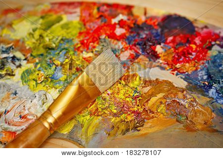 The brush lies on a wooden palette with oil paints. Artistic accessories. Creative tools of self-expression.