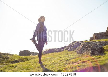 Young Fitness Woman Stretching her Legs in the Mountains in Sun Rays. Female Runner Doing Stretches Outdoor. Healthy Lifestyle Concept.