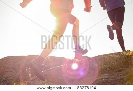 Young Couple Running on the Rocky Trail in the Mountains at Sunset or in the Morning. Active Lifestyle Concept