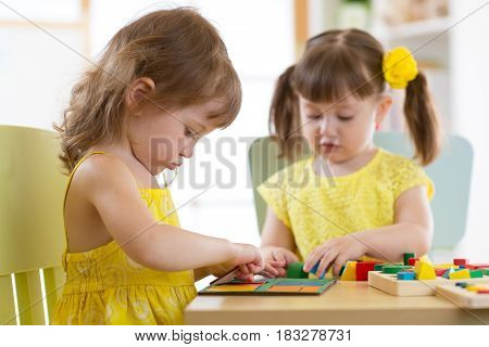 Kids girls playing with logical toy on desk in nursery room or kindergarten. Children arranging and sorting shapes, colors and sizes.