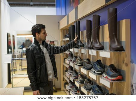 portrait of young male customer choosing rubber boots or watertights gums at supermarket store