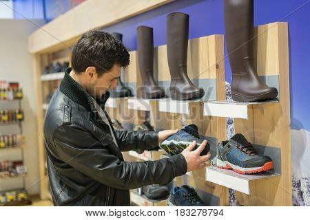 portrait of young male customer choosing sneakers at supermarket store. He is taking shoes from shelf.