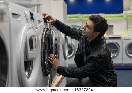 portrait of male customer choosing washing machine in supermarket store