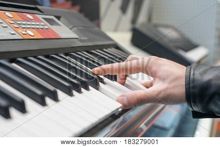 piano keyboard synthesizer with hand playing on it